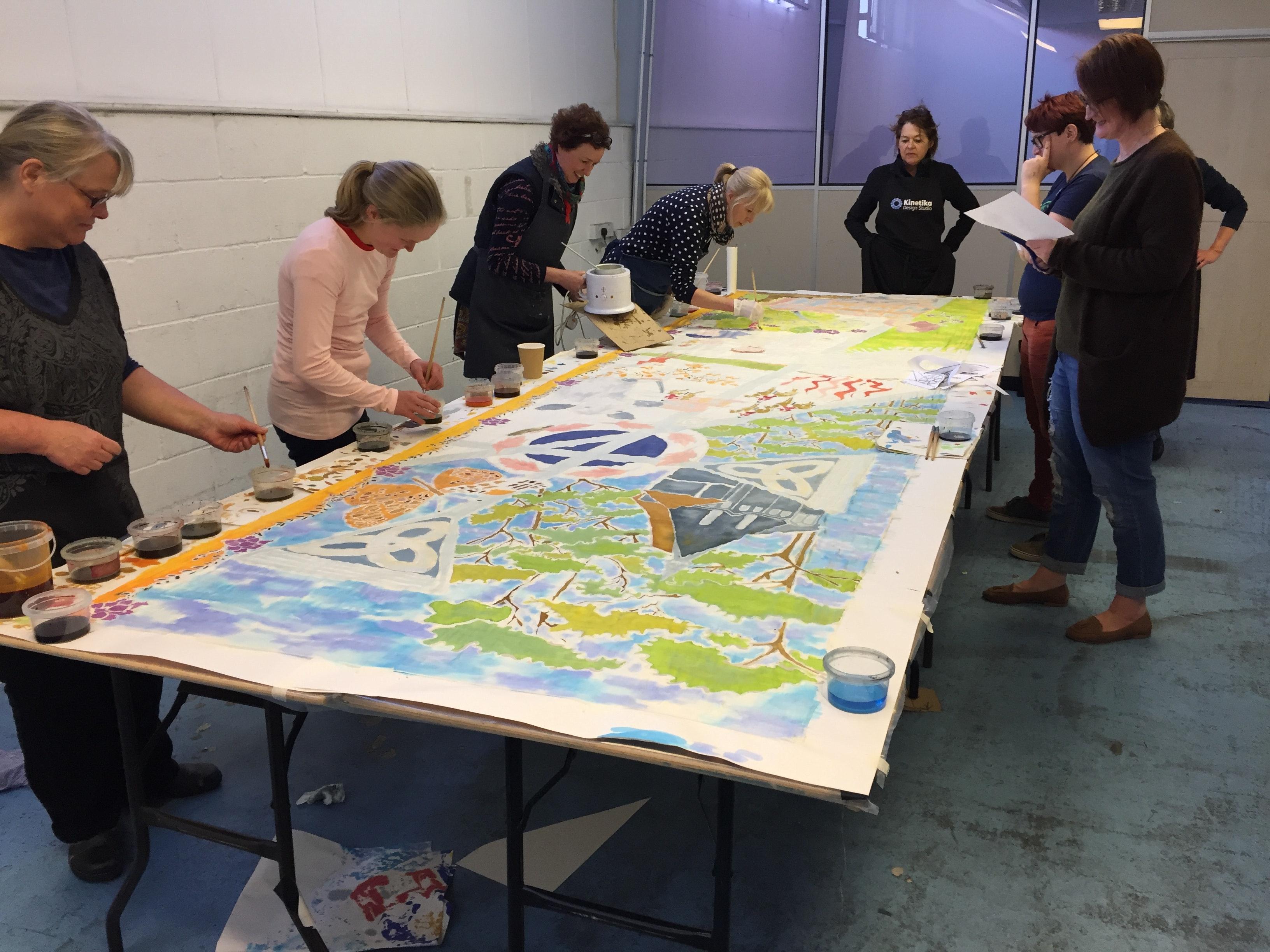 Volunteers working on one of the ten silk banners